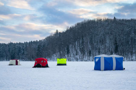 Ice fishing tent on a frozen lake at sunset. Fisherman camp on a peaceful winter evening. Stock fotó