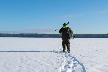 Man with fishing equipment walking on a frozen lake into the distance on a sunny winter day. Banco de Imagens