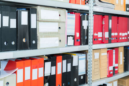 Colourful blank blind folders with files in the shelf. Archival, stacks of documents at the office or library. Physical document storage units