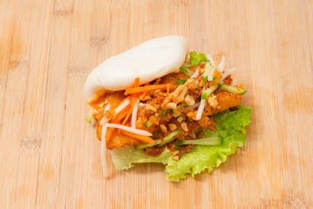 Delicious steamed bao bun on wooden table with fried chicken and fresh vegetables - salad, carrots and roasted peanuts. Popular street food Stock fotó