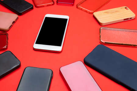 Choice of multicolored plastic back covers for mobile phones on red background with a smart phone on the side Banco de Imagens