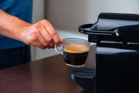 Close up of hand picking up a cup of espresso of capsule coffee machine at home. Concept of coffee break.