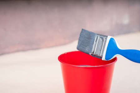 Paint brush and a bucket with paint next to a building exterior wall. Painting house plinth outside. Home renovation. Nobody