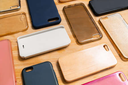 Pile of multicolored plastic back covers for mobile phone. Choice of smart phone protector accessories on wooden background. A lot of silicone phone backs or skins next to each other, pattern