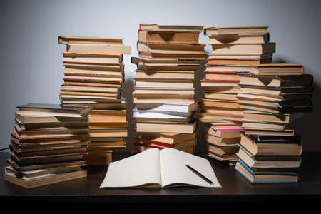 Big stack of books on the table. Studying before the exam. Pile of vintage books. Concept of education and studying