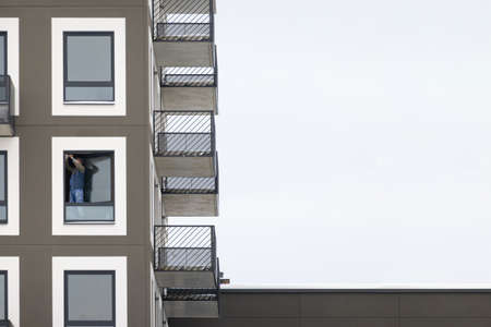 Carpenter installing a window high up in an apartment block. Contractor fixing a glass window. Stock fotó