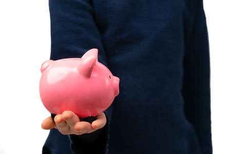 Close up of young entrepreneur holding piggy bank. Financial education for kids. Banco de Imagens
