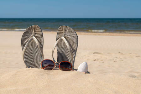 Grey sandals at the beach on a beautiful sunny day. Slippers in the sand by the sea. Flip flops at the shore by the ocean. Banco de Imagens