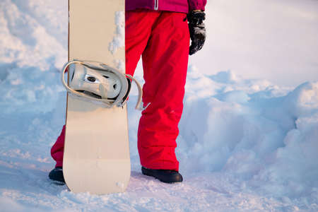 Snowboarder holding a snowboard on top of the mountain and looking reflecting into a distance. Winter holidays. Banco de Imagens