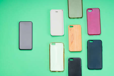 Choice of multicolored plastic back covers for mobile phones on green background with a smart phone on the side Banco de Imagens
