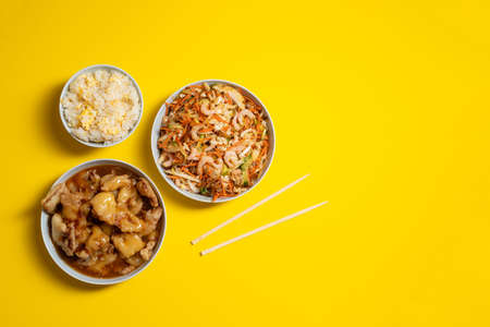 Vibrant plate of shrimp salad, crunchy chicken, bowl of rice with egg and chopsticks on yellow background. Take away food. Stock fotó
