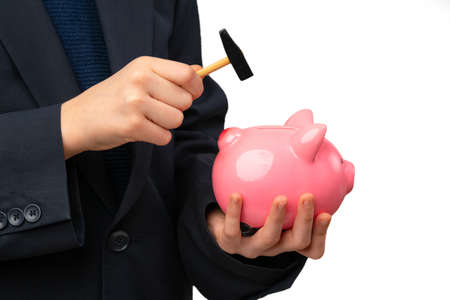 Close up of young entrepreneur hitting piggy bank with a hammer.