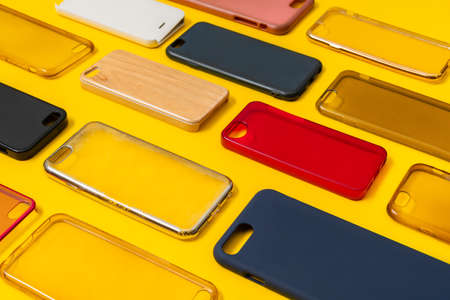 Pile of multicolored plastic back covers for mobile phone. Choice of smart phone protector accessories on yellow background. A lot of silicone phone backs or skins next to each other Stock fotó