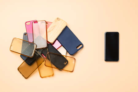 Choice of multicolored plastic back covers for mobile phones on neutral background with a smart phone on the side