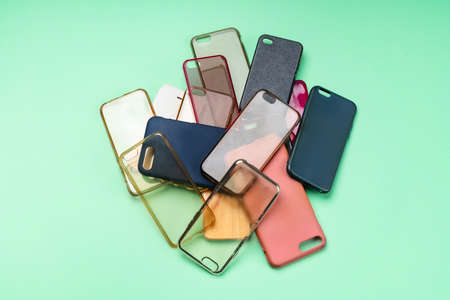 Pile of multicolored plastic back covers for mobile phones on green background