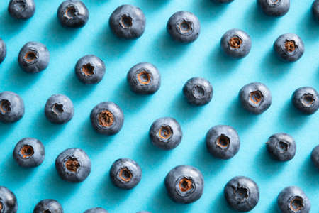 Blueberry pattern on blue background. Ripe blueberries texture close up. Stock fotó