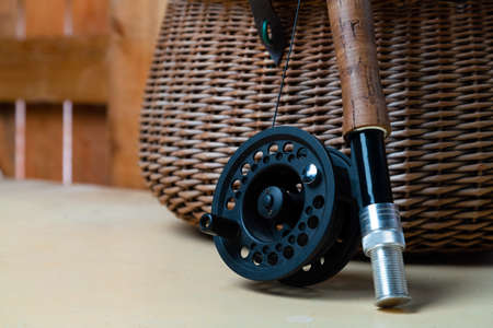 Close up of fly fishing rod with reel next to braided basket. Fly fishing equipment still life. Nobody Stock fotó
