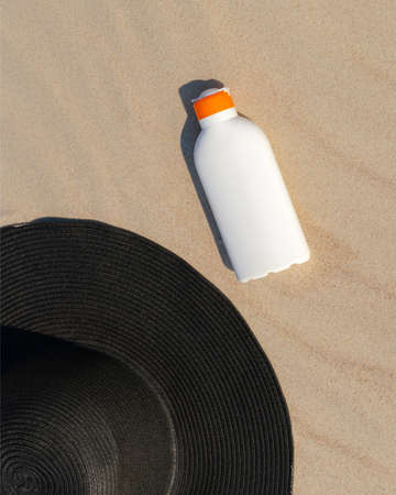 Sunscreen lotion next to a black hat on the sand on a sunny day at the beach. Kin protection cosmetic for sunbathing. Nobody