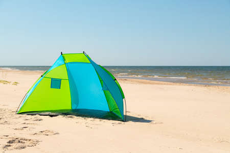 Wind breaker tent on a sandy beach by the sea. Nobody. Colorful tent protection from wind and sunburn. Stock fotó