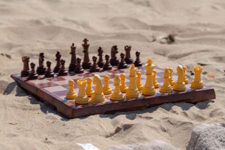 Chess play on the board at the beach. Chessboard on the sand on a sunny day. Stock fotó