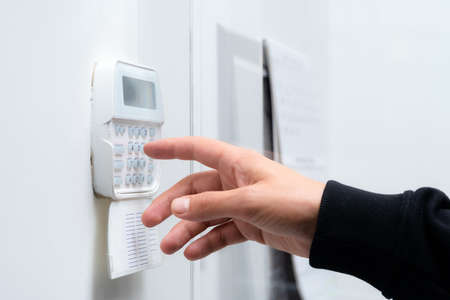 Hand entering alarm system password of an apartment, home or business office. Surveillance and protection console against rubbery and thief Stock fotó