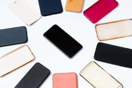 Pile of multicolored plastic back covers for mobile phone on white background. Choice of smart phone protector accessories. A lot of silicone phone backs or skins next to smart phone