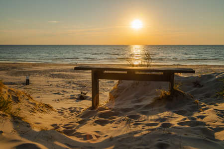 Empty wooden bench and beautiful golden sunset at the beach. Sun setting into the sea on tranquil evening. Nobody