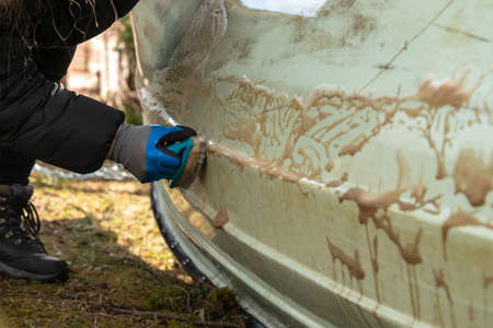 Close up of hand with gloves scrubbing dirt of the boat surface outside. Sailboat maintenance. Stock fotó