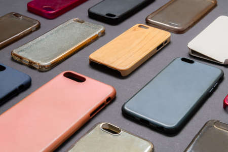 Pile of multicolored plastic back covers for mobile phone. Choice of smart phone protector accessories on black background. A lot of silicone phone backs or skins next to each other