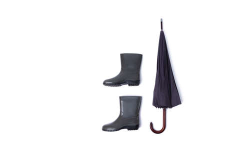 Rubber shoes and umbrella isolated on white background. Rain season and weather forecast. Nobody