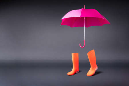 Rubber shoes and umbrella isolated on black background. Rain season and weather forecast. Nobody