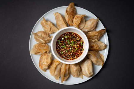 Fried gyoza style dumplings in a plate with spicy soy sauce on black background. Take away asian food.