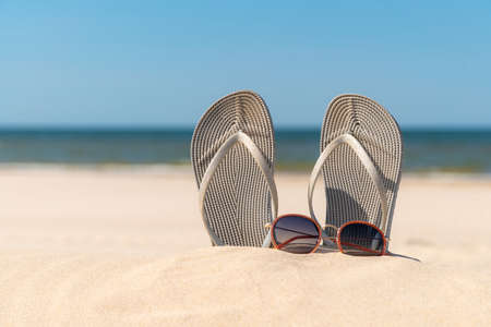 Grey sandals at the beach on a beautiful sunny day. Slippers in the sand by the sea. Flip flops at the shore by the ocean. Banque d'images