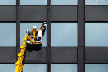Male window cleaner cleaning glass windows on modern building high in the air on a lift platform. Worker polishing glass high in the air