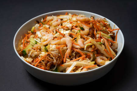 Vibrant plate of shrimp salad. Traditional prawn salad with vegetables. Colorful bowl with seafood on black background. Banque d'images