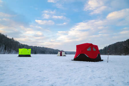 Ice fishing tent on a frozen lake at sunset. Fisherman camp on a peaceful winter evening. Banque d'images