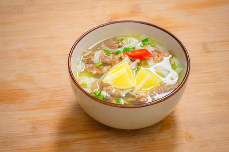 Spicy pho soup bowl with beef meat, lemon slice and chilli peppers on wooden table. Home delivery