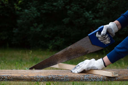 Close up of carpenter wearing gloves and hand sawing wooden plank with old blunt saw in the garden.