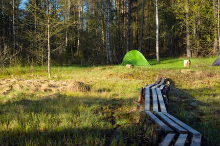 Camping tent set up near the lake in the forest. Relaxing in a camp site outdoors.