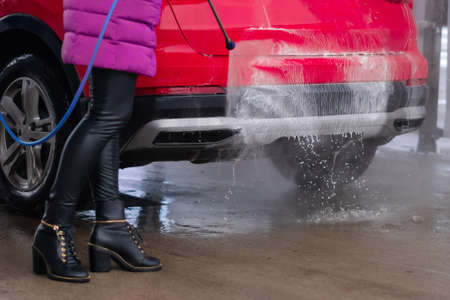 Close up of woman washing the car with high pressure water at self service car wash. Banque d'images