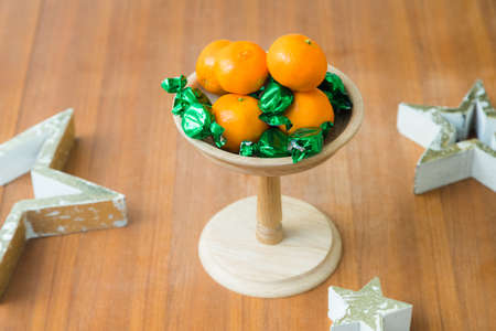Christmas or birthday themed wooden tray stand with sweets and tangerines on the table Banque d'images