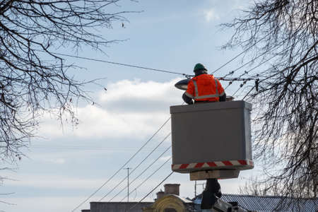 Electrician in a lift platform wearing protective work clothes changing public street lights on a sunny day.