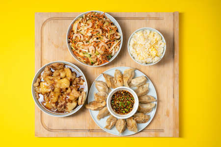 Colorful palette of asian take away food - prawn salad, sweet crunchy chicken, rice and fried dumplings on wooden background Banque d'images