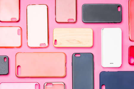 Pile of multicolored plastic back covers for mobile phone. Choice of smart phone protector accessories on pink background. A lot of silicone phone backs or skins next to each other