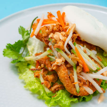 Delicious steamed bao bun on a plate with fried chicken and fresh vegetables - salad, carrots and roasted peanuts. Popular street food