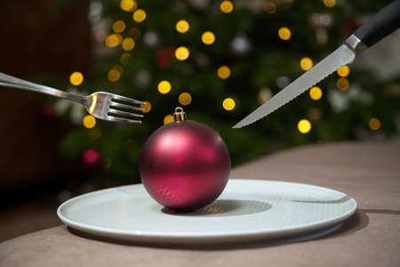 Christmas dinner idea - red tree ball on a plate with out of focus lights in the background