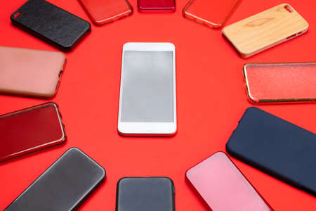 Choice of multicolored plastic back covers for mobile phones on red background with a smart phone on the side Banque d'images