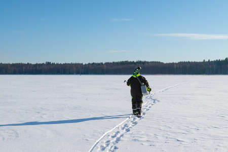 Man with fishing equipment walking on a frozen lake into the distance on a sunny winter day. Banque d'images