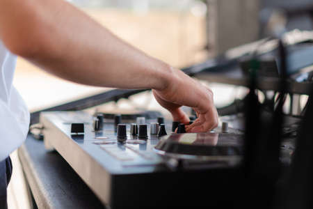 DJ playing music at outdoor event. Person operating mixer at music festival. Close up shot of deejay mixing at the party