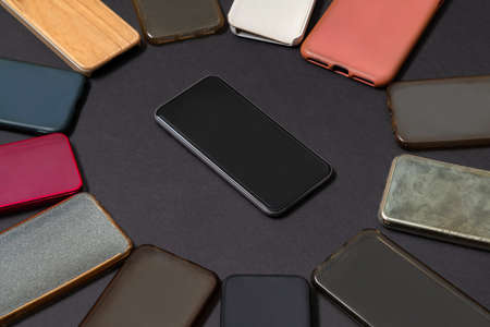 Pile of multicolored plastic back covers for mobile phones on black background with a phone on the side